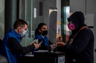 Migration workers check a passenger at El Dorado international airport in Bogota on May 18, 2020. (Photo by Juan BARRETO / AFP) (Photo by JUAN BARRETO/AFP via Getty Images)