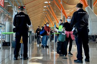 Spanish police officers check on passengers upon their arrival from Paris on May 16, 2020 at the Madrid-Barajas Adolfo Suarez airport in Barajas. - Spain began yesterday to beef up screening of international travellers arriving at its airports, taking their temperature and imposing a 14-day quarantine to prevent a resurgence of the coronavirus in the country. The government also began to restrict arrivals of foreigners who do not usually reside in Spain, with the exception of border workers, health personnel, diplomats and transporters. The new measures will remain in force until June 15, the interior ministry said yesterday. (Photo by GABRIEL BOUYS / AFP) (Photo by GABRIEL BOUYS/AFP via Getty Images)