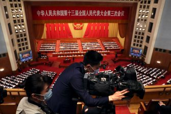 epa08436699 A videographer wearing a face mask films during the opening session of China's National People's Congress (NPC) at the Great Hall of the People in Beijing, China, 22 May 2020. China held the Chinese People's Political Consultative Conference (CPPCC) on 21 May and will hold the National People's Congress (NPC) on 22 May, after the two major political meetings initially planned to be held in March 2020 were postponed amid the ongoing coronavirus COVID-19 pandemic.  EPA/Ng Han Guan / POOL
