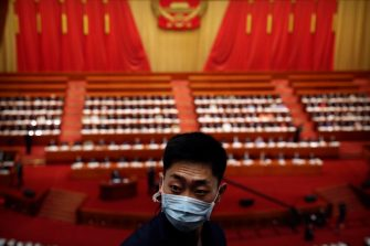 epa08436698 A staff member wearing a face mask stands uring the opening session of China's National People's Congress (NPC) at the Great Hall of the People in Beijing, China, 22 May 2020. China held the Chinese People's Political Consultative Conference (CPPCC) on 21 May and will hold the National People's Congress (NPC) on 22 May, after the two major political meetings initially planned to be held in March 2020 were postponed amid the ongoing coronavirus COVID-19 pandemic.  EPA/Ng Han Guan / POOL