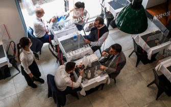 A general view shows people having lunch at tables partitioned with plexiglas at the Goga Cafe on May 18, 2020 in central Milan during the country's lockdown aimed at curbing the spread of the COVID-19 infection, caused by the novel coronavirus. - Restaurants and churches reopen in Italy on May 18, 2020 as part of a fresh wave of lockdown easing in Europe and the country's latest step in a cautious, gradual return to normality, allowing businesses and churches to reopen after a two-month lockdown. (Photo by Miguel MEDINA / AFP) (Photo by MIGUEL MEDINA/AFP via Getty Images)