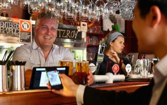 SYDNEY, AUSTRALIA - SEPTEMBER 19:  In this photo illustration, The Old Fitzroy Pub owner Garry Pasfield serves a customer using bitcoins on September 19, 2013 in Sydney, Australia. The Old Fitzroy pub in Sydney's eastern suburbs will accept the digital currency, Bitcoin,  as of Next Sunday.  Using a smartphone and a QR code scanning application customers will be able to purchase beer and menu items at the bar. The Old Fitzroy is the first Australian pub to accept Bitcoin payment.  (Photo by Cameron Spencer/Getty Images)