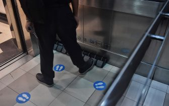 A man uses a foot pedal to select a floor level installed in an elevator for a hands free operation as a preventive measure against the spread of the COVID-19 coronavirus at a shopping mall in Bangkok on May 22, 2020. (Photo by Lillian SUWANRUMPHA / AFP) (Photo by LILLIAN SUWANRUMPHA/AFP via Getty Images)