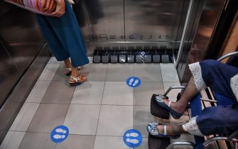 People enter an elevator installed with foot pedals to select a floor level for a hands free operation as a preventive measure against the spread of the COVID-19 coronavirus at a shopping mall in Bangkok on May 22, 2020. (Photo by Lillian SUWANRUMPHA / AFP) (Photo by LILLIAN SUWANRUMPHA/AFP via Getty Images)