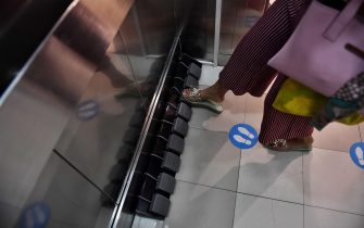 A woman uses a foot pedal to select a floor level installed in an elevator for a hands free operation as a preventive measure against the spread of the COVID-19 coronavirus at a shopping mall in Bangkok on May 22, 2020. (Photo by Lillian SUWANRUMPHA / AFP) (Photo by LILLIAN SUWANRUMPHA/AFP via Getty Images)