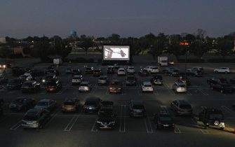 """HICKSVILLE, NEW YORK - MAY 21: In an aerial view from a drone, attendees watch the movie """"The Goonies"""" at a pop-up drive-in theatre built in the parking lot at the Broadway Commons on May 21, 2020 in Hicksville, New York. The function was organized as a partnership between Broadway Commons and Ishevents as organizations look to keep people entertained while maintaining social distance. (Photo by Bruce Bennett/Getty Images)"""