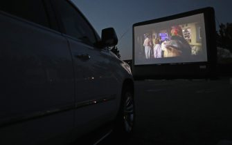 """HICKSVILLE, NEW YORK - MAY 21: Attendees watch the movie """"The Goonies"""" at a pop-up drive-in theatre built in the parking lot at the Broadway Commons on May 21, 2020 in Hicksville, New York. The function was organized as a partnership between Broadway Commons and Ishevents as organizations look to keep people entertained while maintaining social distance. (Photo by Bruce Bennett/Getty Images)"""