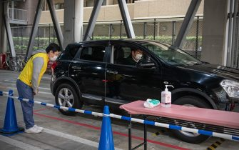 YOKOHAMA, JAPAN - MAY 22: A Chinatown restaurant employee bows as a customer leaves a drive-thru collection point in a car park on May 22, 2020 in Yokohama, Japan. A number of restaurants in Yokohama's Chinatown have adapted to customer concerns about dining out during the Covid-10 coronavirus outbreak by setting up a drive-thru facility at a nearby car park where pre-ordered food can be collected from a member of the restaurant staff. (Photo by Carl Court/Getty Images)