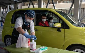 YOKOHAMA, JAPAN - MAY 22: A Chinatown restaurant employee applies hand sanitiser before handing over a food order to a customer at a drive-thru collection point in a car park on May 22, 2020 in Yokohama, Japan. A number of restaurants in Yokohama's Chinatown have adapted to customer concerns about dining out during the Covid-10 coronavirus outbreak by setting up a drive-thru facility at a nearby car park where pre-ordered food can be collected from a member of the restaurant staff. (Photo by Carl Court/Getty Images)