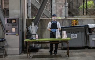 YOKOHAMA, JAPAN - MAY 22: A Chinatown restaurant employee waits for a customer to collect a food order at a drive-thru collection point in a car park on May 22, 2020 in Yokohama, Japan. A number of restaurants in Yokohama's Chinatown have adapted to customer concerns about dining out during the Covid-10 coronavirus outbreak by setting up a drive-thru facility at a nearby car park where pre-ordered food can be collected from a member of the restaurant staff. (Photo by Carl Court/Getty Images)