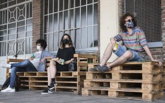 TURIN, ITALY - MAY 21: Young people with protective masks drink relaxed sitting at a distance from each other for the rules of social distancing inside the Docks Dora of Turin on May 21, 2020 in Turin, Italy. The Docks Dora in Turin are an old general warehouse complex located in the Barriera di Milano district in the northern suburbs of Turin. The mercantile plant, originally a railway exchange between Turin-Milan, had been abandoned in the 1960s and over the decades until the 1990s, the complex was re-used for multiple purposes, such as commercial, tertiary, cultural and entertainment activities. Restaurants, bars, cafes, hairdressers and other shops have reopened, subject to social distancing measures, after more than two months of a nationwide lockdown meant to curb the spread of Covid-19. (Photo by Stefano Guidi/Getty Images)