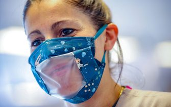 A woman wears a mouth masks with a transparent window for deaf people who do lipreading, at a sheltered workshop (maatwerkbedrijf - entreprise de travail adapte) in Evere, Brussels, on May 15, 2020 amid the pandemic of novel coronavirus (COVID-19). - Belgium is in its ninth week of confinement. (Photo by BRUNO FAHY / Belga / AFP) / Belgium OUT (Photo by BRUNO FAHY/Belga/AFP via Getty Images)