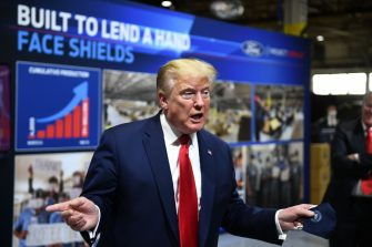 US President Donald Trump  holds a mask as he speaks during a tour of the Ford Rawsonville Plant in Ypsilanti, Michigan on May 21, 2020. (Photo by Brendan Smialowski / AFP) (Photo by BRENDAN SMIALOWSKI/AFP via Getty Images)