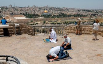 A woman grabs pictures of the Old City of Jerusalem and the closed al-Aqsa Mosque compound, as Palestinian men perform the last Friday prayer of the Muslim holy month of Ramadan at the Mount of Olives on May 22, 2020, amid the novel coronavirus pandemic crisis. (Photo by AHMAD GHARABLI / AFP) (Photo by AHMAD GHARABLI/AFP via Getty Images)