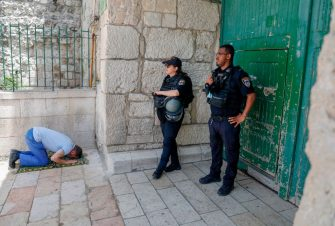 Israeli security forces look on as a Palestinian worshipper performs the last Friday prayer of the Muslim holy month of Ramadan, outside the closed al-Aqsa mosque compound in the Old City of Jerusalem, amid the novel coronavirus pandemic crisis, on May 22, 2020. (Photo by AHMAD GHARABLI / AFP) (Photo by AHMAD GHARABLI/AFP via Getty Images)