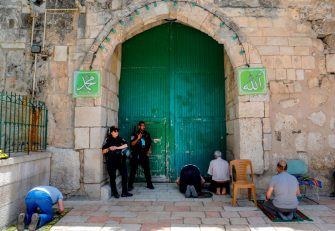 Israeli security forces look on as Palestinian worshippers perform the last Friday prayer of the Muslim holy month of Ramadan, outside the closed al-Aqsa mosque compound in the Old City of Jerusalem, amid the novel coronavirus pandemic crisis, on May 22, 2020. (Photo by AHMAD GHARABLI / AFP) (Photo by AHMAD GHARABLI/AFP via Getty Images)