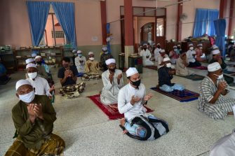 Muslim men wear face masks as they practice social distancing while praying in the Yakaniah mosque for the first Friday prayers in eight weeks due to restrictions to contain the COVID-19 coronavirus, for Eid al-Fitr that marks the end of the Muslim holy month of Ramadan, in the southern Thai province of Narathiwat on May 22, 2020. (Photo by Madaree TOHLALA / AFP) (Photo by MADAREE TOHLALA/AFP via Getty Images)