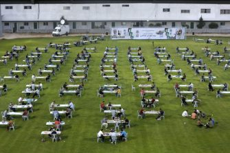 Palestinians break their Ramadan fast during an Iftar meal set-up to respect social distancing measures amid the COVID-19 pandemic, organized by the Islamic Hamas movement which runs the besieged Gaza Strip, at the Palestine football stadium in Gaza city on May 21, 2020, ahead of launching a digital campaign to mark al-Quds (Jerusalem) international day. - While Israelis celebrate their 1967 capture of the eastern part of the holy city, Palestinians commemorate the day with events marking the Palestinian and Muslim connection to the holy city. (Photo by MOHAMMED ABED / AFP) (Photo by MOHAMMED ABED/AFP via Getty Images)