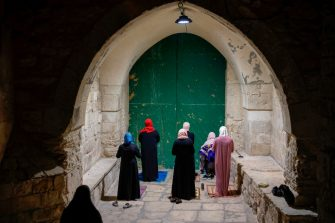 Palestinian Muslim women worshippers, distanced from each other due to the COVID-19 coronavirus pandemic, pray outside the closed gate of the Aqsa mosque compound in the Old City of Jerusalem, as they mark Lailat al-Qadr, one of the holiest nights during the Muslim fasting month of Ramadan reckoned by some to fall on the 27th night, late on May 19, 2020. - Lailat al-Qadr (Night of Destiny) marks the night Muslims believe the first verses of the Koran were revealed to the Prophet Mohammed through the archangel Gabriel. (Photo by AHMAD GHARABLI / AFP) (Photo by AHMAD GHARABLI/AFP via Getty Images)