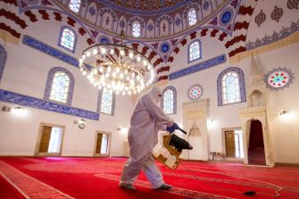 TOPSHOT - A worker sprays disinfectant inside the Banya Bashi Mosque in Sofia, to prevent the spread of the COVID-19, the novel coronavirus, before the last Friday prayer of the fasting month of Ramadan on May 22, 2020. (Photo by NIKOLAY DOYCHINOV / AFP) (Photo by NIKOLAY DOYCHINOV/AFP via Getty Images)