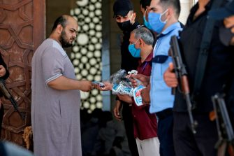 A man hands face masks to Palestinian worshippers attending the last Friday prayer of the fasting month of Ramadan on May 22, 2020, at al-Omari  mosque in Gaza City, after the local authorities allowed mosques to reopen amid the easing of some restrictions enacted to mitigate the spread of the novel coronavirus. (Photo by MAHMUD HAMS / AFP) (Photo by MAHMUD HAMS/AFP via Getty Images)