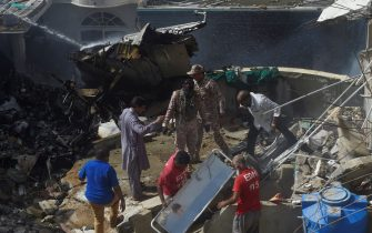 Rescue workers gather at the site after a Pakistan International Airlines flight crashed in a residential neighbourhood in Karachi on May 22, 2020. - A Pakistan passenger plane with more than 100 people believed to be on board crashed in the southern city of Karachi on May 22, the country's aviation authority said. (Photo by Asif HASSAN / AFP) (Photo by ASIF HASSAN/AFP via Getty Images)