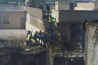 EDITORS NOTE: Graphic content / Rescue workers evacuate an injured victim from the site after a Pakistan International Airlines aircraft crashed in a residential neighbourhood in Karachi on May 22, 2020. - A Pakistan passenger plane with more than 100 people believed to be on board crashed in the southern city of Karachi on May 22, the country's aviation authority said. (Photo by Asif HASSAN / AFP) (Photo by ASIF HASSAN/AFP via Getty Images)