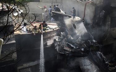 Firefighters spray water on the wreckage of a Pakistan International Airlines aircraft after it crashed at a residential area in Karachi on May 22, 2020. - A Pakistani passenger plane with nearly 100 people on board crashed into a residential area of the southern city of Karachi on May 22. (Photo by Rizwan TABASSUM / AFP) (Photo by RIZWAN TABASSUM/AFP via Getty Images)