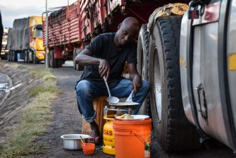 A picture taken on May 5, 2020, shows a truck driver preparing an Iftar, the evening meal which Muslims end their daily Ramadan fasting, beside his truck as he has been waiting for five days to be tested for the COVID-19 coronavirus before entering to Kenya as its mandatory for all drivers at Namanga, northern Tanzania. (Photo by Filbert RWEYEMAMU / AFP) (Photo by FILBERT RWEYEMAMU/AFP via Getty Images)