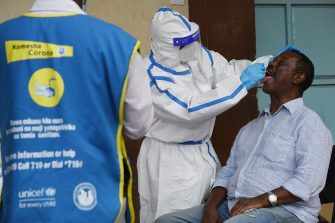 A Kenyan health worker takes an oral swab from a resident of Eatstleigh, during a mass testing exercise for the COVID-19 coronavirus in Nairobi on May 20, 2020. (Photo by SIMON MAINA / AFP) (Photo by SIMON MAINA/AFP via Getty Images)