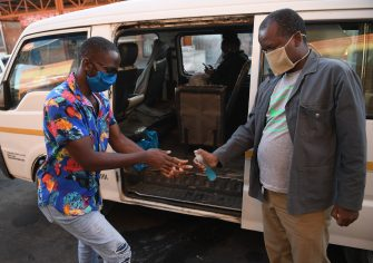 A man receives hand sanitiser as a preventive measure against the spread of the COVID-19 coronavirus before boarding a taxi in Gaborone on May 21, 2020. - Botswana President Mokgweetsi Masisi ended the 48-day national lockdown on May 21, 2020 but kept some restrictions, including movement between regions. Wearing of face masks remains mandatory and non-compliance attracts a fine of 5,000 pula ($412). (Photo by Monirul Bhuiyan / AFP) (Photo by MONIRUL BHUIYAN/AFP via Getty Images)