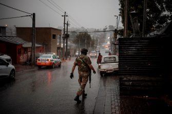 A South African National Defence Force (SANDF) soldier patrols under a heavy downpour during a mixed patrol of the SANDF and the Johannesburg Metro Police Department in Alexandra township in Johannesburg, on April 14, 2020. (Photo by Michele Spatari / AFP) (Photo by MICHELE SPATARI/AFP via Getty Images)