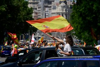 """Demonstrators wave Spanish flags during a """"caravan for Spain and its freedom"""" protest by far-right party Vox against the Spanish government in Madrid on May 23, 2020. - Spain, one of the most affected countries in the world by the novel coronavirus with 28,628 fatalities, has extended until June 6 the state of emergency which significantly limits the freedom of movement to fight the epidemic. The left-wing government's management of the crisis has drawn a barrage of criticism from righ-wing parties who have denounced its """"brutal confinement"""". (Photo by JAVIER SORIANO / AFP) (Photo by JAVIER SORIANO/AFP via Getty Images)"""