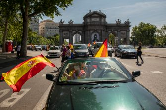 MADRID, SPAIN - MAY 23: People hold Spanish flags as they take part on an in-vehicle protest against the Spanish government on May 23, 2020 in Madrid, Spain. Far right wing VOX party has called for in-vehicle protests across Spain against the Spanish government's handling of the Covid-19 pandemic. Spain has imposed some of the tightest restrictions across the world to contain the spread of the virus, but measures are now easing. Most of the Spanish population supports the lockdown according to a survey. (Photo by Pablo Blazquez Dominguez/Getty Images)
