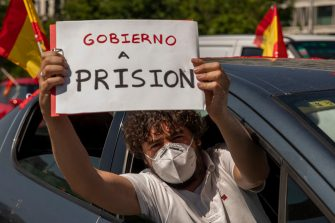MADRID, SPAIN - MAY 23: A man holds a placard reading 'Government to prison' during an in-vehicle protest against the Spanish government on May 23, 2020 in Madrid, Spain. Far right wing VOX party has called for in-vehicle protests across Spain against the Spanish government's handling of the Covid-19 pandemic. Spain has imposed some of the tightest restrictions across the world to contain the spread of the virus, but measures are now easing. Most of the Spanish population supports the lockdown according to a survey. (Photo by Pablo Blazquez Dominguez/Getty Images)