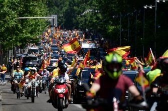"""Demonstrators take part in a """"caravan for Spain and its freedom"""" protest by far-right party Vox against the Spanish government in Madrid on May 23, 2020. - Spain, one of the most affected countries in the world by the novel coronavirus with 28,628 fatalities, has extended until June 6 the state of emergency which significantly limits the freedom of movement to fight the epidemic. The left-wing government's management of the crisis has drawn a barrage of criticism from righ-wing parties who have denounced its """"brutal confinement"""". (Photo by JAVIER SORIANO / AFP) (Photo by JAVIER SORIANO/AFP via Getty Images)"""
