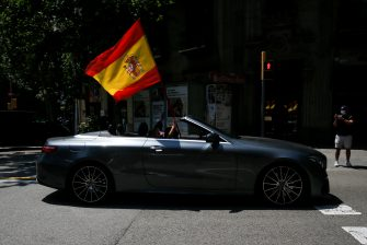"""Demonstrators wave a Spanish flag from a convertible during a """"caravan for Spain and its freedom"""" protest by far-right party Vox in Barcelona on May 23, 2020. - Spain, one of the most affected countries in the world by the novel coronavirus with 28,628 fatalities, has extended until June 6 the state of emergency which significantly limits the freedom of movement to fight the epidemic. The left-wing government's management of the crisis has drawn a barrage of criticism from righ-wing parties who have denounced its """"brutal confinement"""". (Photo by Pau Barrena / AFP) (Photo by PAU BARRENA/AFP via Getty Images)"""