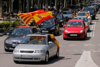 """Demonstrators wave Spanish flags during a """"caravan for Spain and its freedom"""" protest by far-right party Vox in Barcelona on May 23, 2020. - Spain, one of the most affected countries in the world by the novel coronavirus with 28,628 fatalities, has extended until June 6 the state of emergency which significantly limits the freedom of movement to fight the epidemic. The left-wing government's management of the crisis has drawn a barrage of criticism from righ-wing parties who have denounced its """"brutal confinement"""". (Photo by Pau Barrena / AFP) (Photo by PAU BARRENA/AFP via Getty Images)"""