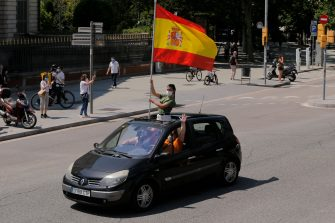 """Demonstrators wave a Spanish flag from inside a car during a """"caravan for Spain and its freedom"""" protest by far-right party Vox in Barcelona on May 23, 2020. - Spain, one of the most affected countries in the world by the novel coronavirus with 28,628 fatalities, has extended until June 6 the state of emergency which significantly limits the freedom of movement to fight the epidemic. The left-wing government's management of the crisis has drawn a barrage of criticism from righ-wing parties who have denounced its """"brutal confinement"""". (Photo by Pau Barrena / AFP) (Photo by PAU BARRENA/AFP via Getty Images)"""