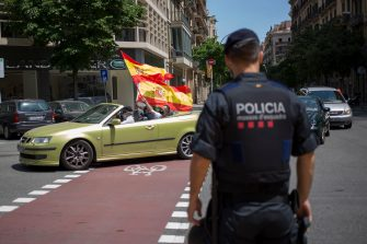 """BARCELONA, SPAIN - MAY 23: Protesters wave a flag in front of the police on May 23, 2020 in Barcelona, Spain. The far-right political party Vox has called for demonstrations in the Spanish province capitals with the slogan; Caravan for Spain and its freedom. The anti-government demonstration is by car to minimize the risks of contagion from Covid. Some parts of Spain have entered the so-called """"Phase One"""" or """"Phase Two"""" transitions from its coronavirus lockdown, allowing many shops to reopen as well as restaurants who serve customers outdoors. Locations that were harder hit by coronavirus (Covid-19), such as Madrid and Barcelona, remain in a stricter quarantine. (Photo by Manuel Medir/Getty Images)"""