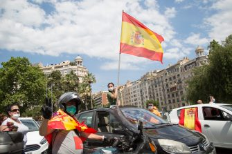 """BARCELONA, SPAIN - MAY 23: A protester waves a Spanish flag from her car on May 23, 2020 in Barcelona, Spain. The far-right political party Vox has called for demonstrations in the Spanish province capitals with the slogan; Caravan for Spain and its freedom. The anti-government demonstration is by car to minimize the risks of contagion from Covid. Some parts of Spain have entered the so-called """"Phase One"""" or """"Phase Two"""" transitions from its coronavirus lockdown, allowing many shops to reopen as well as restaurants who serve customers outdoors. Locations that were harder hit by coronavirus (Covid-19), such as Madrid and Barcelona, remain in a stricter quarantine. (Photo by Manuel Medir/Getty Images)"""
