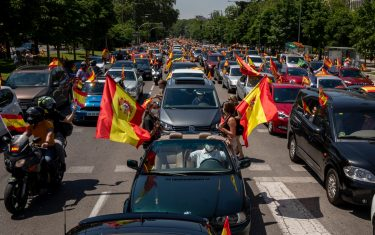 MADRID, SPAIN - MAY 23: People holding Spanish flags take part on an in-vehicle protest against the Spanish government on May 23, 2020 in Madrid, Spain. Far right wing VOX party has called for in-vehicle protests across Spain against the Spanish government's handling of the Covid-19 pandemic. Spain has imposed some of the tightest restrictions across the world to contain the spread of the virus, but measures are now easing. Most of the Spanish population supports the lockdown according to a survey. (Photo by Pablo Blazquez Dominguez/Getty Images)