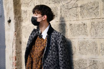 MILAN, ITALY - FEBRUARY 23: A guest wears a black face mask, a gray leopard print coat, a brown wool leopard print pullover, a white shirt, outside BOSS, during Milan Fashion Week Fall/Winter 2020-2021 on February 23, 2020 in Milan, Italy. (Photo by Edward Berthelot/Getty Images)
