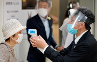 epa08442418 A Matsuya Ginza staff member wearing protective gear checks temperature of a customer during the reopening of the department store's food retailing floor after a month and a half of closure at Tokyo's Ginza shopping district, Japan, 25 May 2020. Following the decline in the COVID-19 coronavirus infections number, the government is to lift the state of emergency restrictions in Tokyo and remaining prefectures later in the day.  EPA/FRANCK ROBICHON