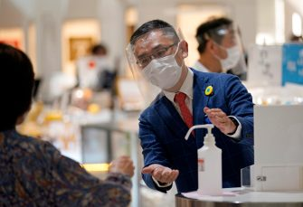 epa08442423 A Matsuya Ginza staff member wearing protective gear invites a customer to use hydroalcoholic solution during the reopening of the department store's food retailing floor after a month and a half of closure at Tokyo's Ginza shopping district, Japan, 25 May 2020. Following the decline in the COVID-19 coronavirus infections number, the government is to lift the state of emergency restrictions in Tokyo and remaining prefectures later in the day.  EPA/FRANCK ROBICHON