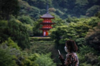 epa08442506 A woman wearing a face mask takes photos with a mobile phone as she visits Kiyomizudera temple in Kyoto, western Japan, 25 May 2020. Japan on 25 May is expected to end its nationwide state of emergency by lifting it in remaining areas including the capital Tokyo. The world's third-biggest economy is set to reopen gradually as the number of new infections decline day by day.  EPA/DAI KUROKAWAA