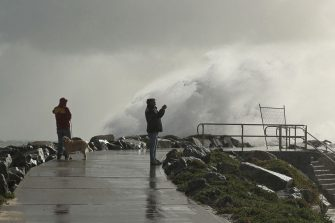 PERTH, AUSTRALIA - MAY 25: A man takes footage on his phone as a large swell hits the rock groyne at Cottesloe Beach on May 25, 2020 in Perth, Australia. Ex-Tropical Cyclone Mangga has brought heavy wind, rain and waves along Western Australia's coastline after combining with other cold fronts to create unprecedented storm conditions. State Emergency Services have answered hundreds of calls for help with structural and roof damage since Sunday while thousands of homes and businesses have been left without power.  (Photo by Paul Kane/Getty Images)