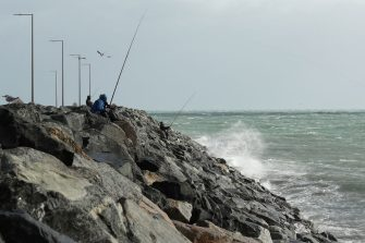 PERTH, AUSTRALIA - MAY 25: Fisherman brave the elements on the rockwall at Port Beach on May 25, 2020 in Perth, Australia. Ex-Tropical Cyclone Mangga has brought heavy wind, rain and waves along Western Australia's coastline after combining with other cold fronts to create unprecedented storm conditions. State Emergency Services have answered hundreds of calls for help with structural and roof damage since Sunday while thousands of homes and businesses have been left without power.  (Photo by Paul Kane/Getty Images)