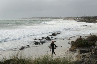 PERTH, AUSTRALIA - MAY 25: A surfer jogs down the beach before entering the water at Port Beach on May 25, 2020 in Perth, Australia. Ex-Tropical Cyclone Mangga has brought heavy wind, rain and waves along Western Australia's coastline after combining with other cold fronts to create unprecedented storm conditions. State Emergency Services have answered hundreds of calls for help with structural and roof damage since Sunday while thousands of homes and businesses have been left without power.  (Photo by Paul Kane/Getty Images)