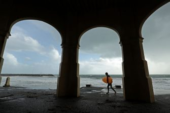 PERTH, AUSTRALIA - MAY 25: A surfer walks past the Indiana Tea House at Cottesloe Beach on May 25, 2020 in Perth, Australia. Ex-Tropical Cyclone Mangga has brought heavy wind, rain and waves along Western Australia's coastline after combining with other cold fronts to create unprecedented storm conditions. State Emergency Services have answered hundreds of calls for help with structural and roof damage since Sunday while thousands of homes and businesses have been left without power.  (Photo by Paul Kane/Getty Images)